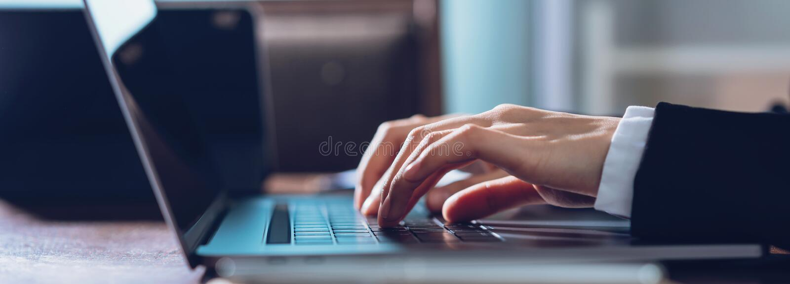 Close up of business woman hands typing on laptop computer and searching web, browsing in the workplace at office. royalty free stock photo