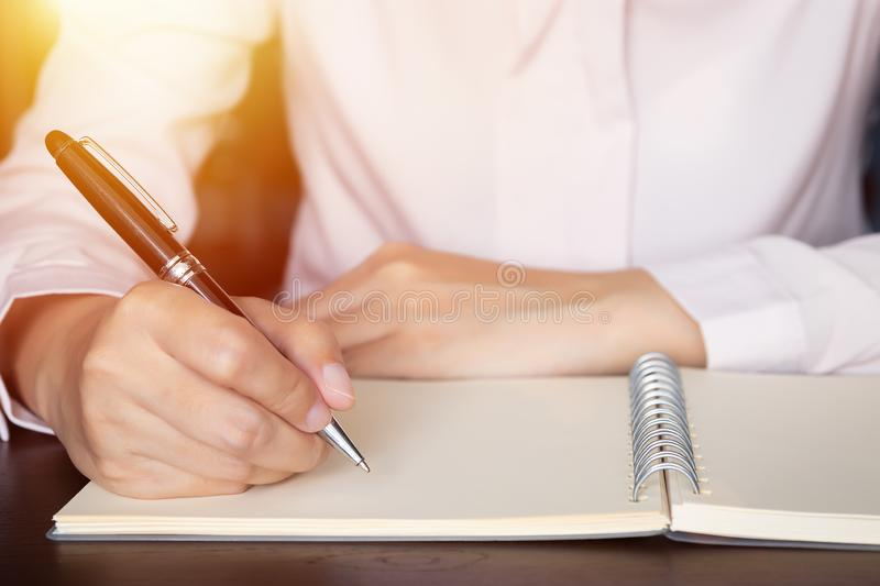 Close up of business woman hands writing in spiral notepad on wooden table. stock images
