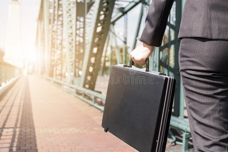 Close up business woman holding black briefcase on the metal bridge walking to work, go to target and goal concept royalty free stock photo