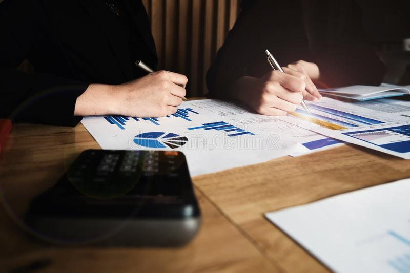 Close up Business woman and partner using calculator for calculating finance, tax, accounting, statistics and analytic research, royalty free stock image