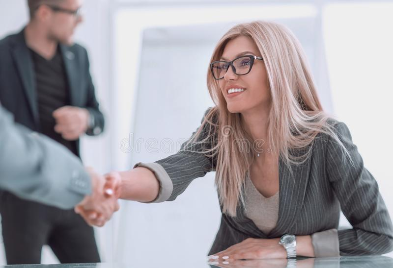 Close up. business woman shaking hands sitting behind a Desk. Close up. business women shaking hands sitting behind a Desk. concept of cooperation stock image