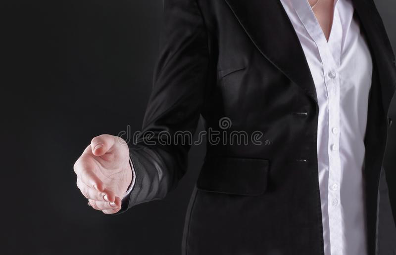 Close up.business woman stretches out her hand for handshake.isolated on black background.  stock photography