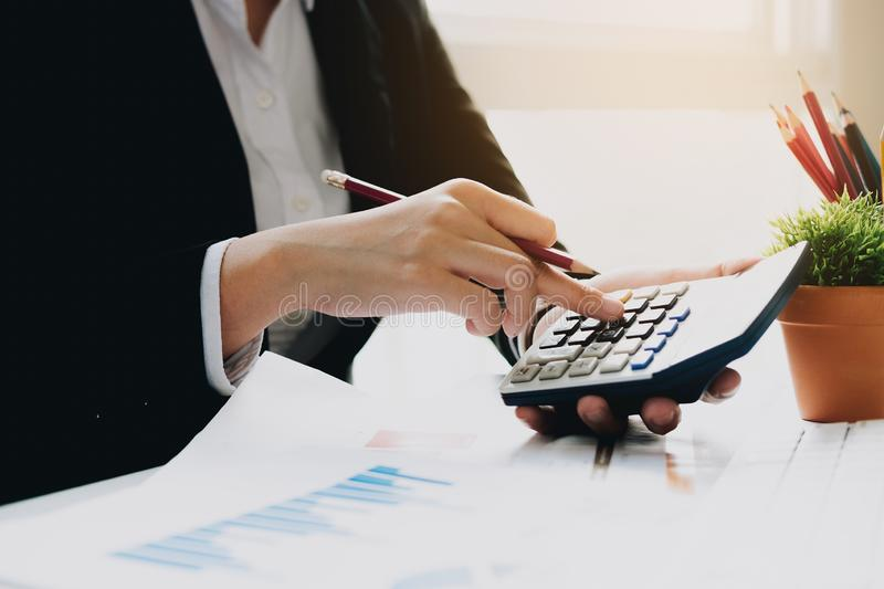 Close up Business woman using calculator for do math finance on wooden desk in office and business working background, tax, stock photos