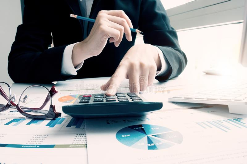 Close up Business woman using calculator and laptop for do math finance on wooden desk in office and business working background, stock image