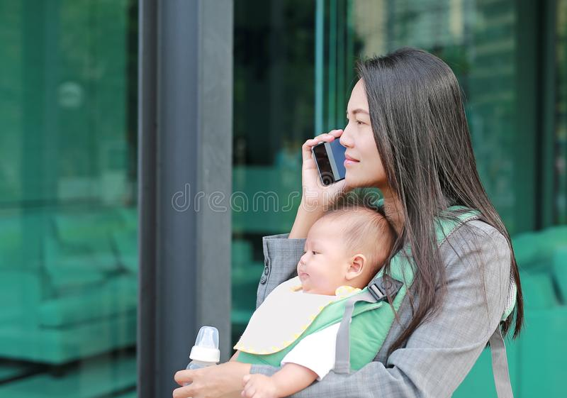 Close up business woman working by telephone with carrying her infant and holding her child`s milk bottle. Busy mother hurrying i stock photos