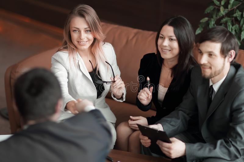 Close up.business woman shaking hands with business partner sitting at work Desk royalty free stock images