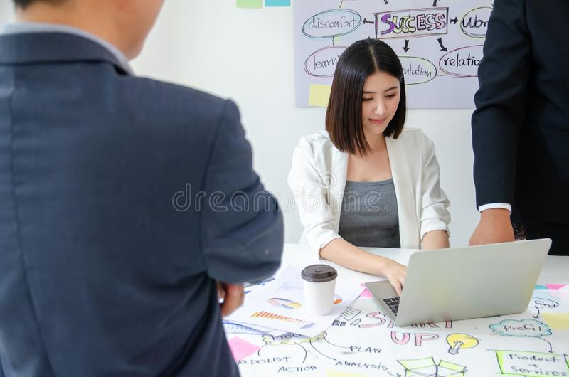 Close-up of businessman and boss or CEO or supervisor follow up the work progress to young businesswoman at desk royalty free stock image