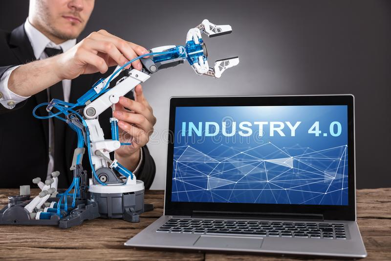 Businessman Building Robot With Laptop Showing Industry 4.0 stock photography
