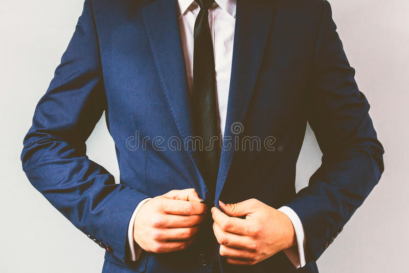 Close up of a businessman buttoning his suit. stock images