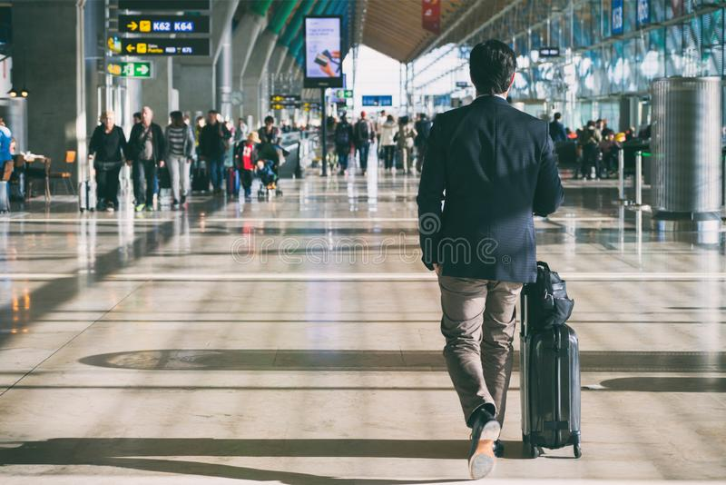 Close up of businessman carrying suitcase while walking through a passenger departure terminal in airport. Businessman traveler royalty free stock photo