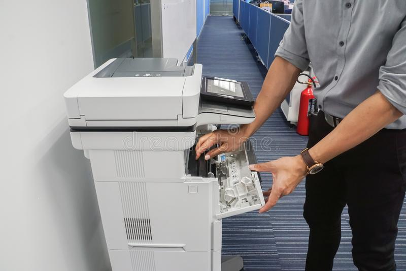 Businessman in grey shirt open the toner cartridge for inkjet printer. Close up businessman in grey shirt open the toner cartridge for inkjet printer royalty free stock image