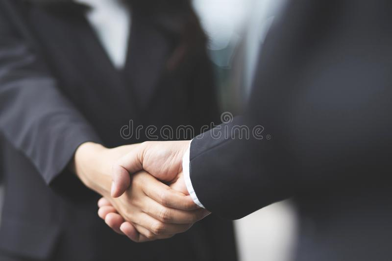 Close up of a businessman hand shake businesswoman between two colleagues royalty free stock photos
