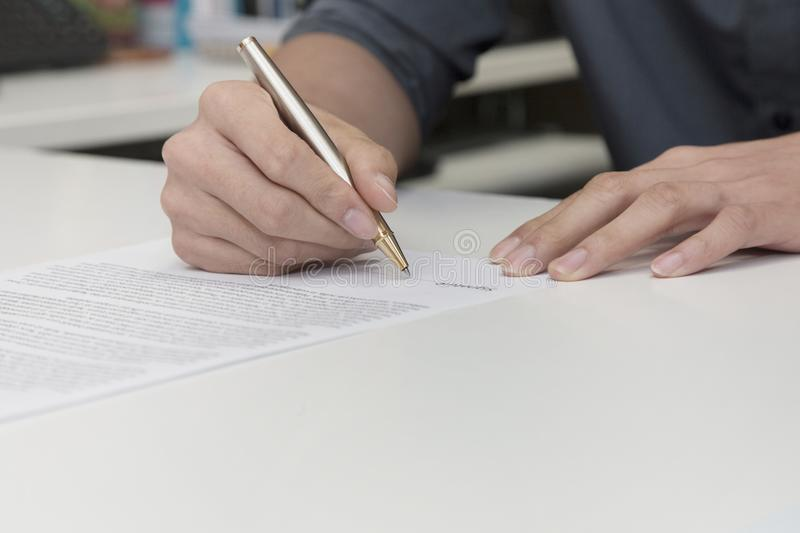 businessman hand signing a contract paper stock photo