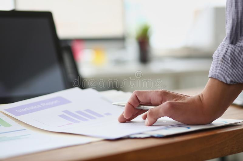 Close-up of businessman hand working with business graph information diagram on wooden desk royalty free stock photos