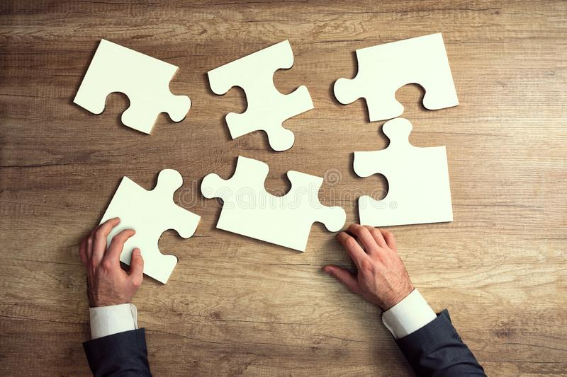 Close-up of businessman hands try to completing jigsaw puzzle royalty free stock images