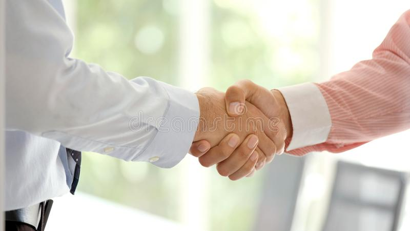 Close up of businessman handshake at office, business cooperation, success in business concept royalty free stock photo