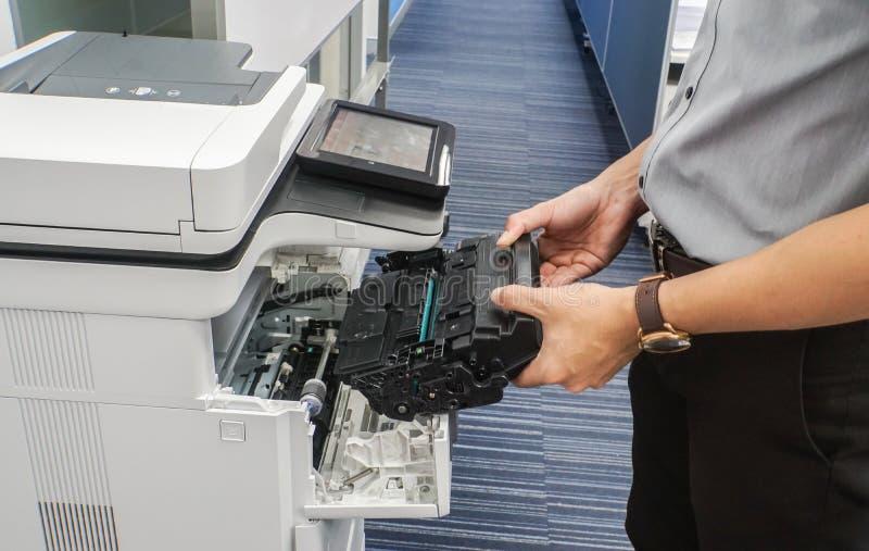 Businessman hold toner cartridge to put into printer feed. Close up businessman hold toner cartridge to put into printer feed royalty free stock photo