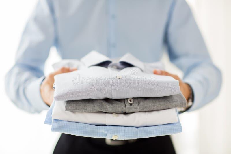 Close up of businessman holding folded shirts royalty free stock images