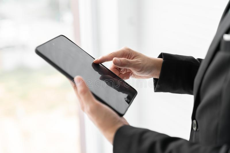 Close up businessman is holding the tablet and pointing his finger on the screen with urban background out of the window. Business royalty free stock images