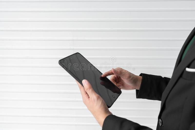 Close up businessman is holding the tablet and pointing his finger on the screen with white background room. Business and technolo stock images