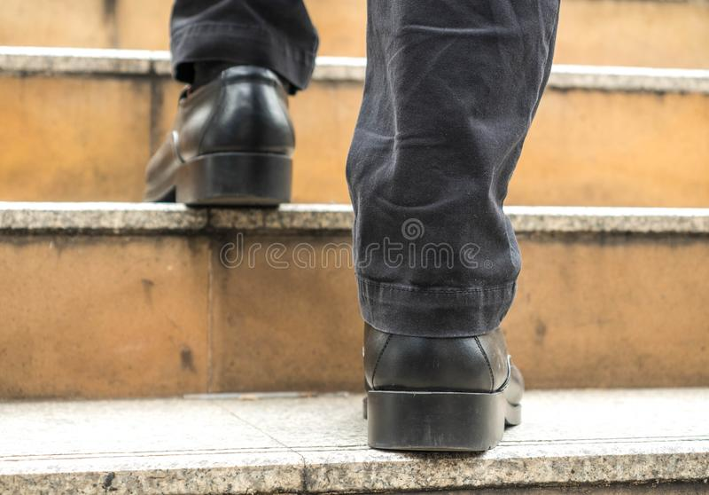 Close up of businessman legs walk up the stone staircase royalty free stock image