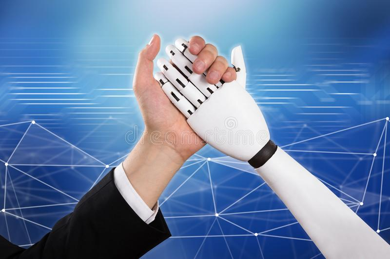 Businessman And Robot Doing Arm Wrestling. Close-up Of Businessman And Robot Doing Arm Wrestling Over Abstract Background stock photos