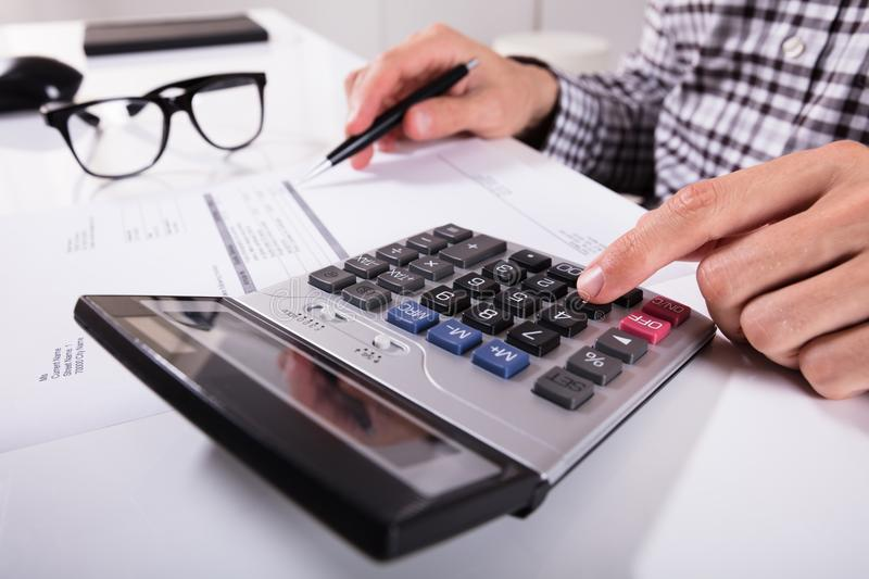 Businessman`s Hands Calculating Invoice. Close-up Of Businessman`s Hands Calculating Invoice Using Calculator With Eyeglasses On Desk stock photos