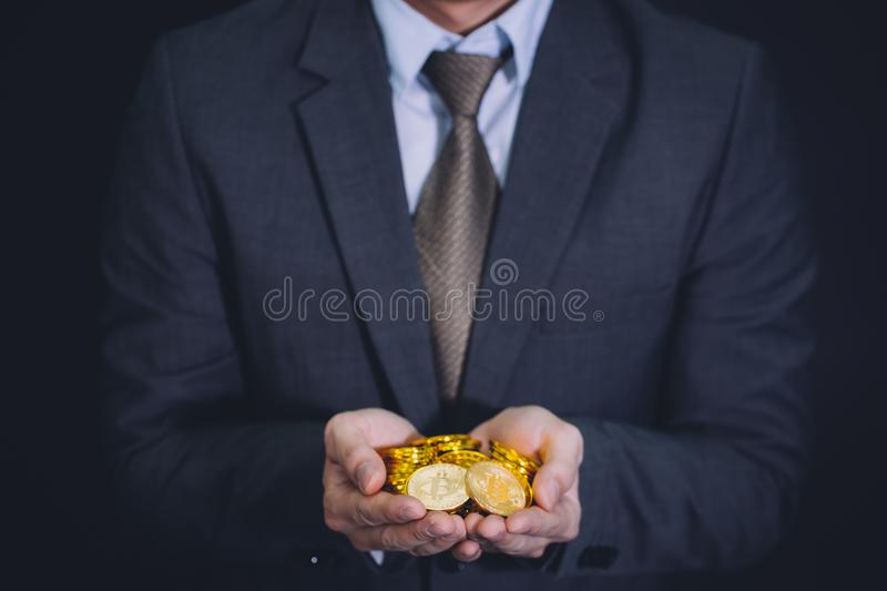 Close-up of businessman`s hands full of bitcoin sign of coins - cryptocurrency financial trade wealth and business investment stock photography