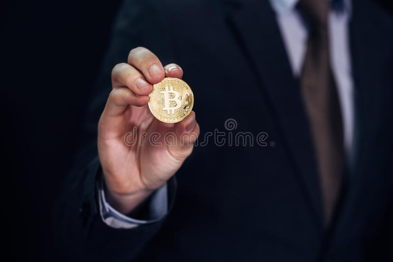 Close-up of businessman showing and holding bitcoin sign of coin - indicating crypto currency and future of digital financial bank. Ing trade royalty free stock images