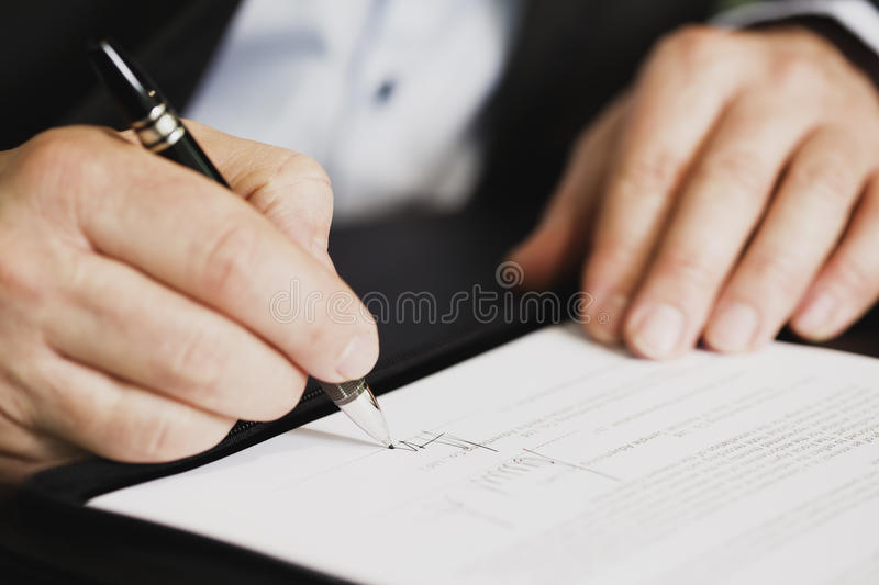 Close up of businessman signing a contract. Businessman sitting at office desk signing a contract with shallow focus on signature royalty free stock photography