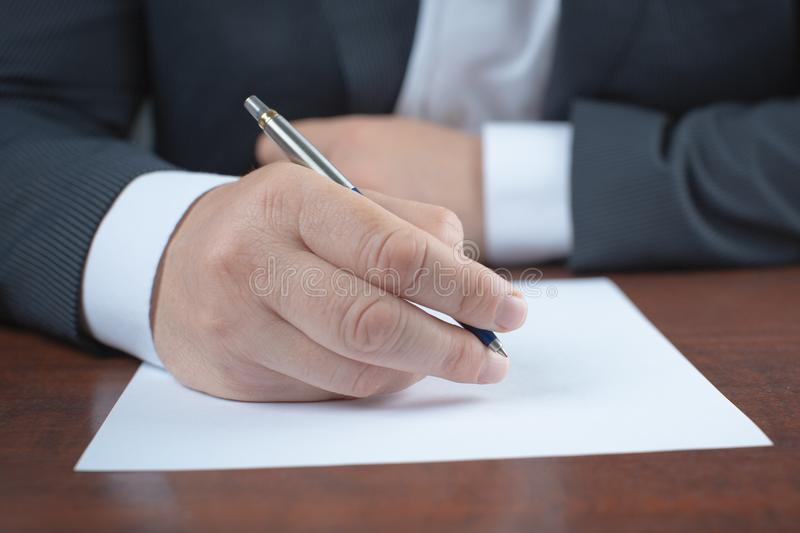 Close-up of a businessman signing an important document. Horizontal royalty free stock photos