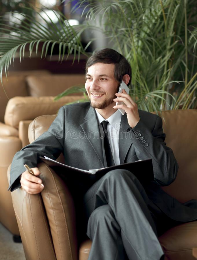 Close up.Businessman sitting in a business center reading documents while having a phone call stock image