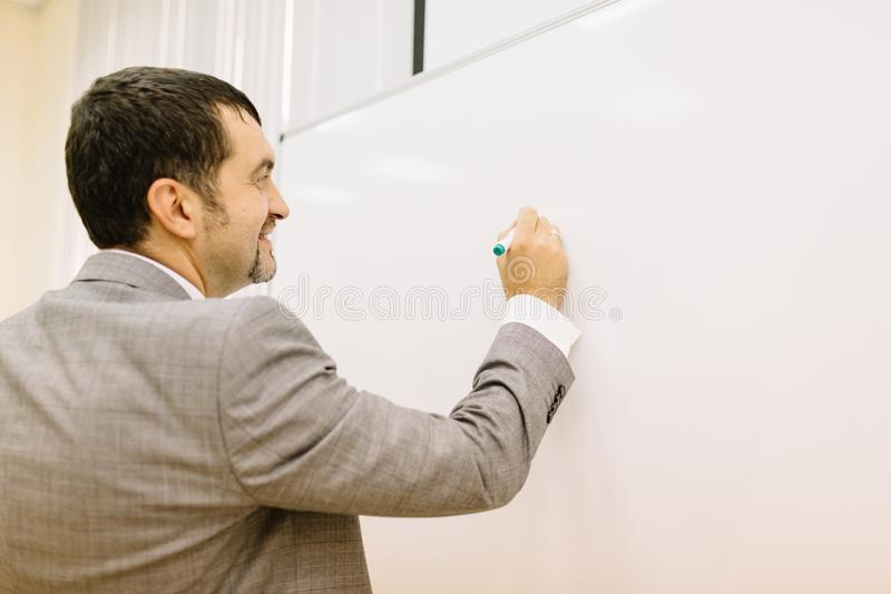Close-up man writing on a light desk background. Lecturer next to a multimedia projector. Teacher work concept. stock photos