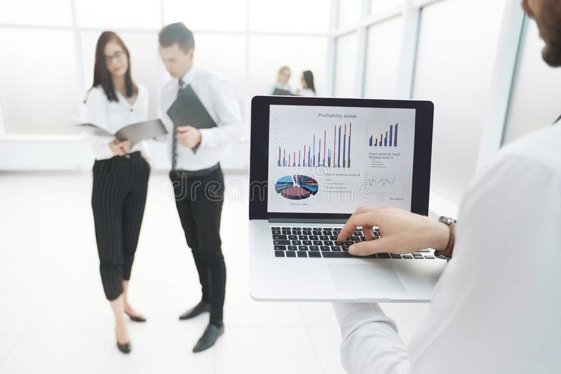 Close up.businessman uses laptop while standing in office lobby stock photo