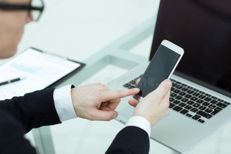 Close up. a businessman uses a smartphone in the workplace stock photo