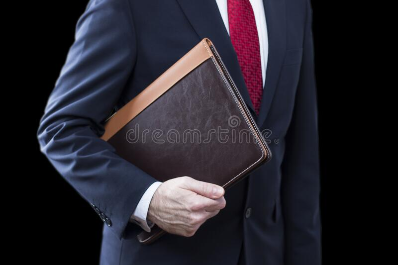 Close up of businessman wearing suit holding documents on black background stock image
