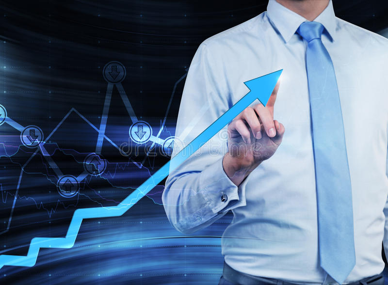 Close-up of the businessman who points out the growing arrow, which symbolises the concept of the success. A graph with drawn arrow signs 'buy' or'sell' on the stock images