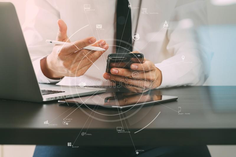 Close up of businessman working with mobile phone on wooden desk in modern office with virtual icon diagram stock photo
