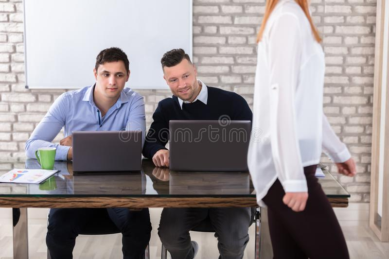 Businessmen Looking At Woman stock images
