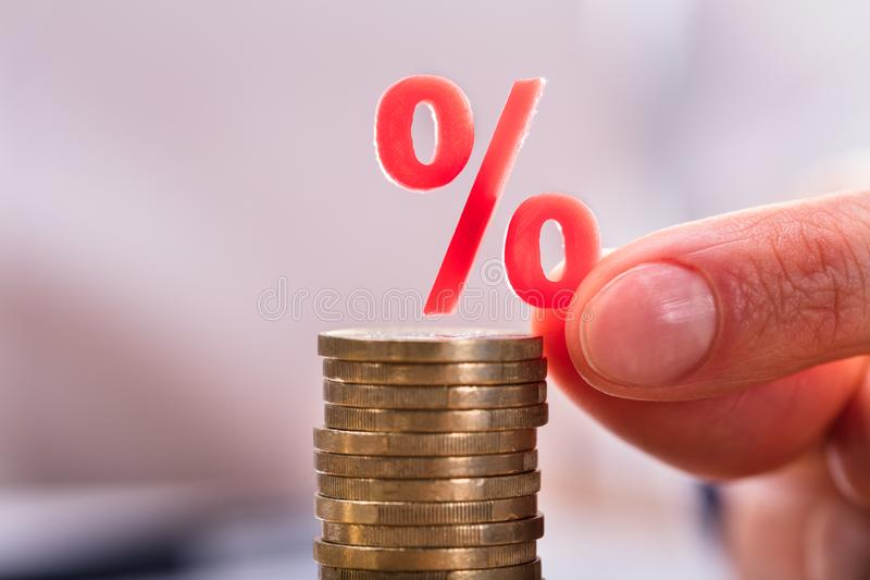 Businessperson`s Placing Percentage Sign Over Stacked Coins stock photos