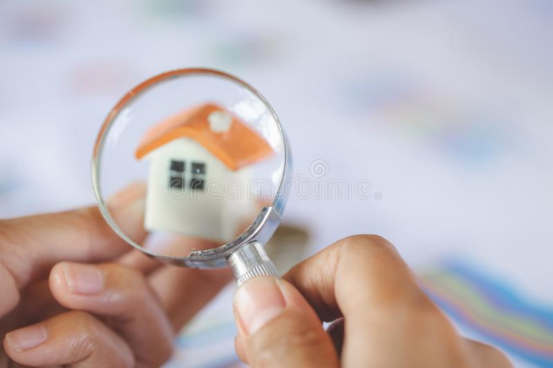 Close-up Of A Businessperson`s Hand Looking At House Model Through Magnifying Glass, House searching concept with a magnifying. Glass royalty free stock photography