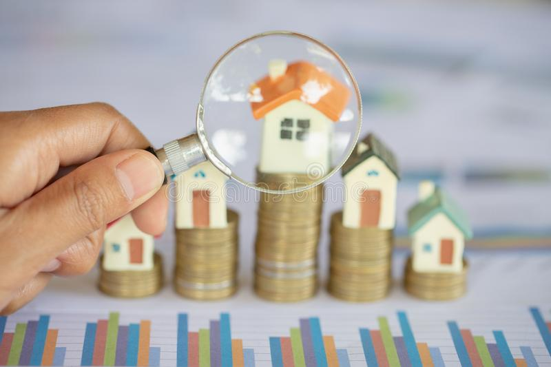 Close-up Of A Businessperson`s Hand Looking At House Model Through Magnifying Glass, House searching concept with a magnifying. Glass stock image