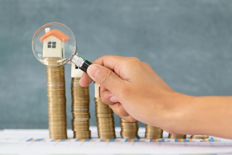 Close-up Of A Businessperson`s Hand Looking At House Model Through Magnifying Glass, House searching concept with a magnifying. Glass royalty free stock image