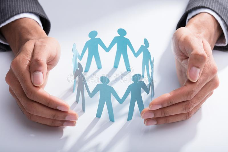 Businessperson Protecting Cut-out Figures. Close-up Of A Businessperson`s Hand Protecting Cut-out Figures On Desk royalty free stock photography