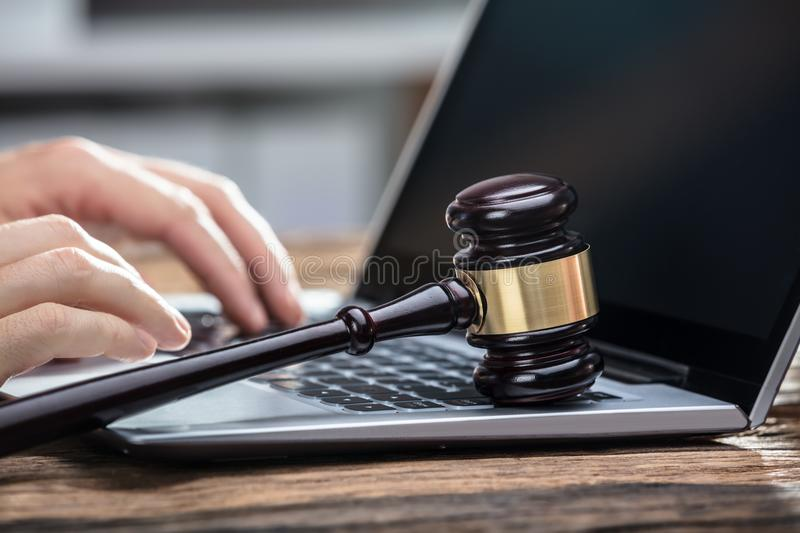 Businessperson`s Hand Using Laptop On Wooden Desk royalty free stock photos