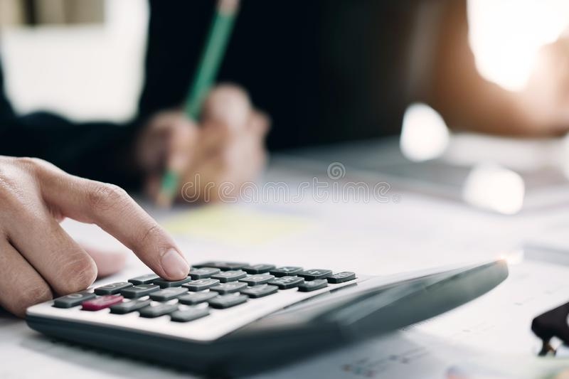 Close up of businesswoman or accountant hand holding pen working on calculator to calculate business data, accountancy document royalty free stock images