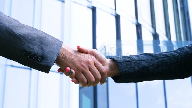 Close up businesswoman and businessman shaking hands Business partnership. Concept of: Skyscraper, Deal, Business building, Archit royalty free stock photo