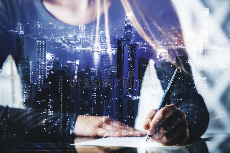 Author and work concept. Close up of businesswoman hands doing paperwork or writing letter at abstract desk with city view. Author and work concept. Double stock images