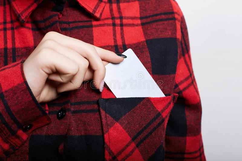 Close up of businesswoman holding blank visiting card. Young female pulling out business card from the pocket of her red checked s. Hirt, , exchanging stock images