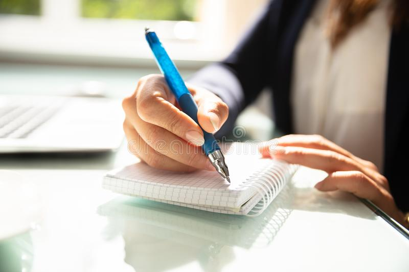 Close-up Of A Businesswoman`s Hand Writing Note In Diary royalty free stock photos